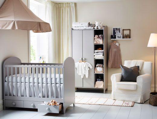 Um quarto para bebé com um berço com gavetas em cinzento claro e um roupeiro Combinado com um dossel em bege e uma poltrona branca