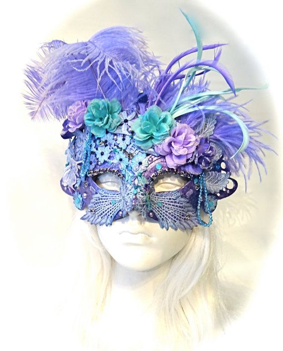 This delicate Venetian masquerade mask is turquoise & lavender with tonal hand dyed lace overlays and sparkle galore! The molded glittered mask has been carefully encrusted with pearls, beads and rhinestones and has plumes of ostrich, biot & marabou feathers. Beaded silk roses are at the crown of this one of a kind creation and the mask ties with organdy ribbons in back. It has a very renaissance feel to it and is perfect for a renaissance masquerade ball. This mask is available to ship…