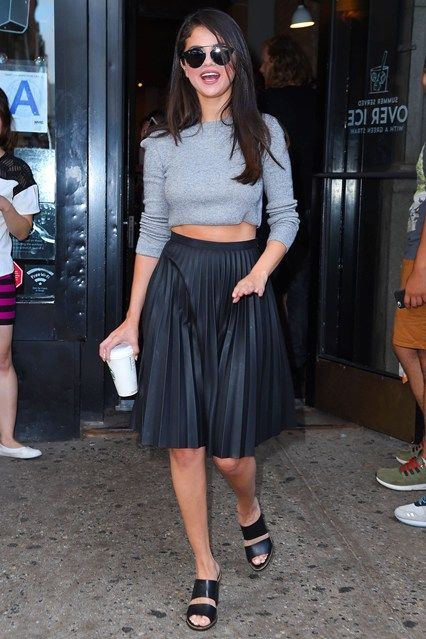 Selena Gomez dresses down her pleated skirt for day time with a simple grey sweater while out and about in New York.