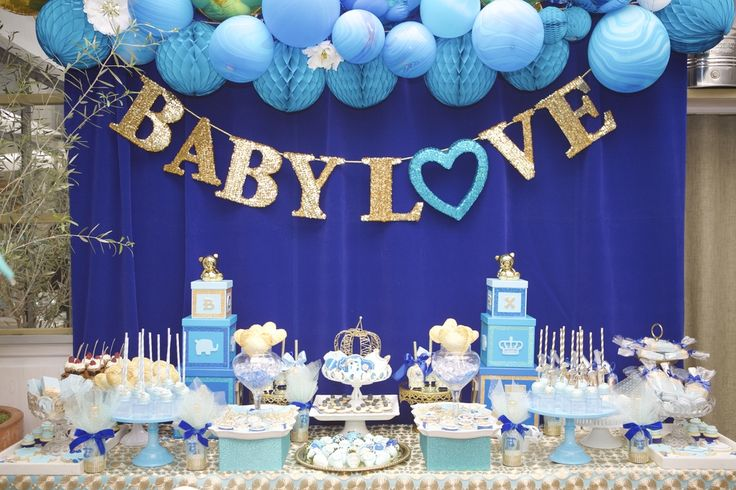 BABY LOVE sweets table design. Dessert table backdrop. Backdrop installation made of balloons and honeycomb tissue paper flowers, gold sequin letter banner sign. Desserts on blue cake plates. | Lovelyfest Event Design | Royal Blue Baby Shower