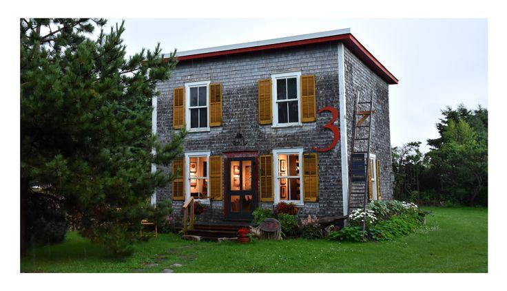 Galerie d'art située à Kamouraska, l'un des plus beaux villages du Québec, dans une coquette dépendance d'autrefois. Mise en valeur de l'architecture d'une maison d'été datant de 1930, un carré de 20 pi x 20 pi, sur deux étages. Couverture de bardeau naturel et d'époque. Volets jaunes ocres et accents décoratifs rouges. Photo sous la pluie.