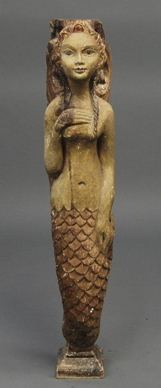 Mermaid Carved folk art painted Mermaid figure. The carved figure of a mermaid has curly hair and has one hand at her chest, 32 1/2x6 1/4x8 ½ inches. Origin unknown.