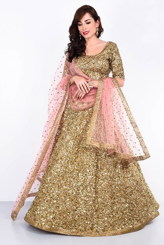 c4a7d8eaa719ba Indian wedding dress trends 2018-shimmering golden lehenga with pink  glittering dupatta-gorgeous