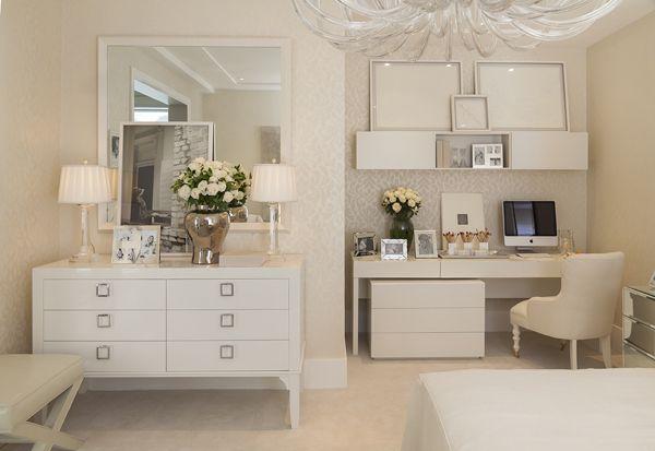Com decoração off-white, o quarto é romântico e contemporâneo ao mesmo tempo, além de muito aconchegante e bem iluminado!. Chris fez uso de texturas nas almofadas e no papel de parede, os espelhos e das mesas de cabebeira espelhadas deram amplitude e um toque moderno, o lustre que faz uma releitura de um clássico é super, e os arranjos de flores deram um toque ainda mais feminino. O cantinho reservado para o home office, igualmente clarinho e organizado, também é uma boa inspiração!