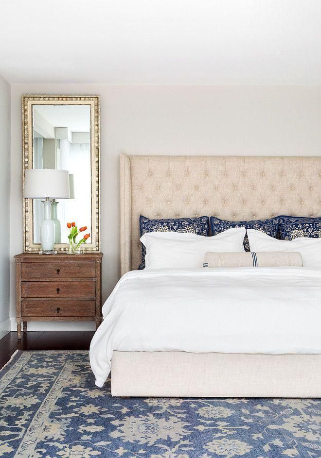 Blue and white decor in the master bedroom. This stunning cream and blue bedroom features a linen tufted wingback bed frame and headboard dressed in white bedding and blue patterned pillows next to a French nightstand, white ceramic table lamp and tall gold mirror.
