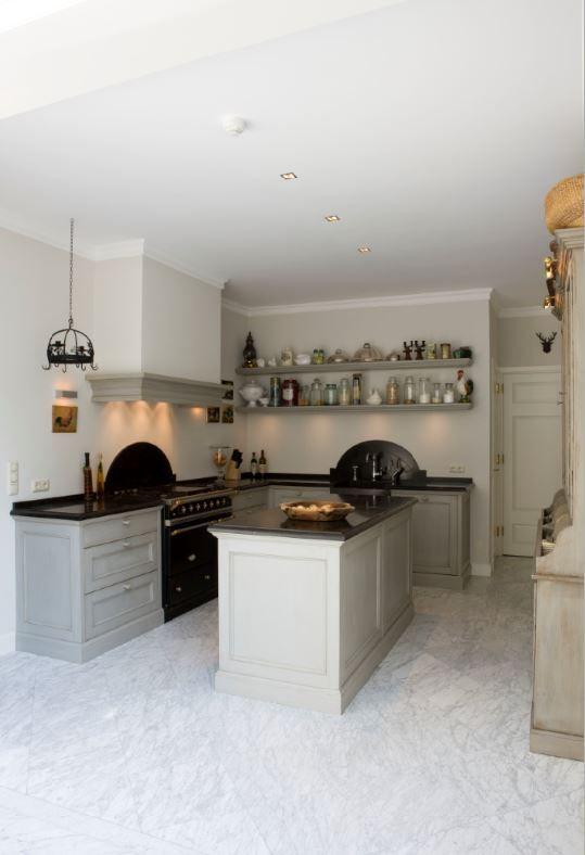 Klassieke keuken in massief 3-laags eiken. Paneelfronten met klokprofiel (klein). Eivormige houten knopjes in kleur van de keuken. Belgisch hardstenen aanrechtbladen met papegaaienbek. Achterwanden en dubbele spoelbak (uit één stuk) ook in Belgisch hardsteen. Fornuis is van Lacanche - The Living Kitchen by Paul van de Kooi