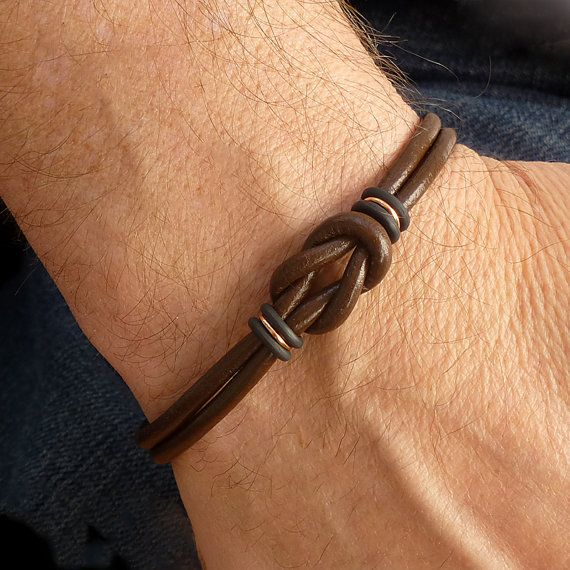 This mens brown leather bracelet in the style of a Celtic bracelet, is made from genuine rich brown leather cord and quality metal cast antiqued copper Zamak hardware. A hypoallergenic, certified lead and nickel free unisex bracelet that closes with a sleek, strong, secure, tube shaped, copper magnetic clasp. The Celtic knot is secured with black rubber o rings and copper jump rings. Made to any bracelet size in the drop down menu. EASY SIZING: Wrist size (measured without slack) + wiggle…
