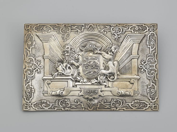 """Zilveren relief. Gietwerk. Voorstelling van het wapen van Friesland, met twee heraldische leeuwen. Het wapen en de leeuwen zijn geplaatst in een decor van perspectivische kolommen en krulewerken. In een cartouche """"Frisia"""". Leeuwarden."""