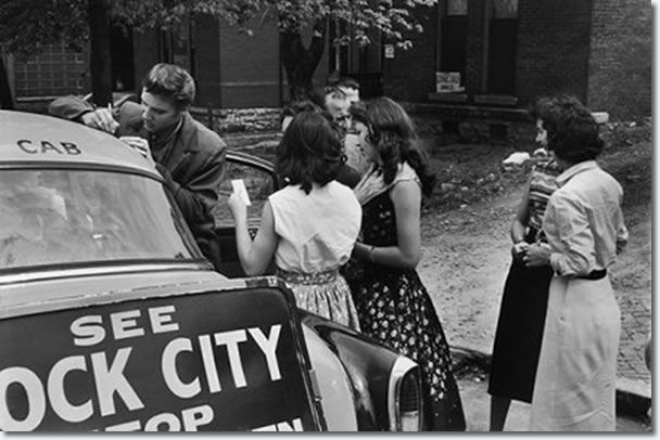 Elvis signing autographs for fans as he leaves the studio : April 14, 1956.