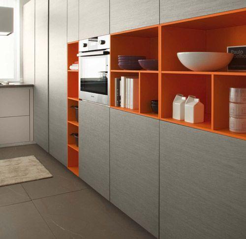 Cocina Moderna con acabados en madera estratificada, meson en Silestone y muebles abiertos lacados en colores vivos.