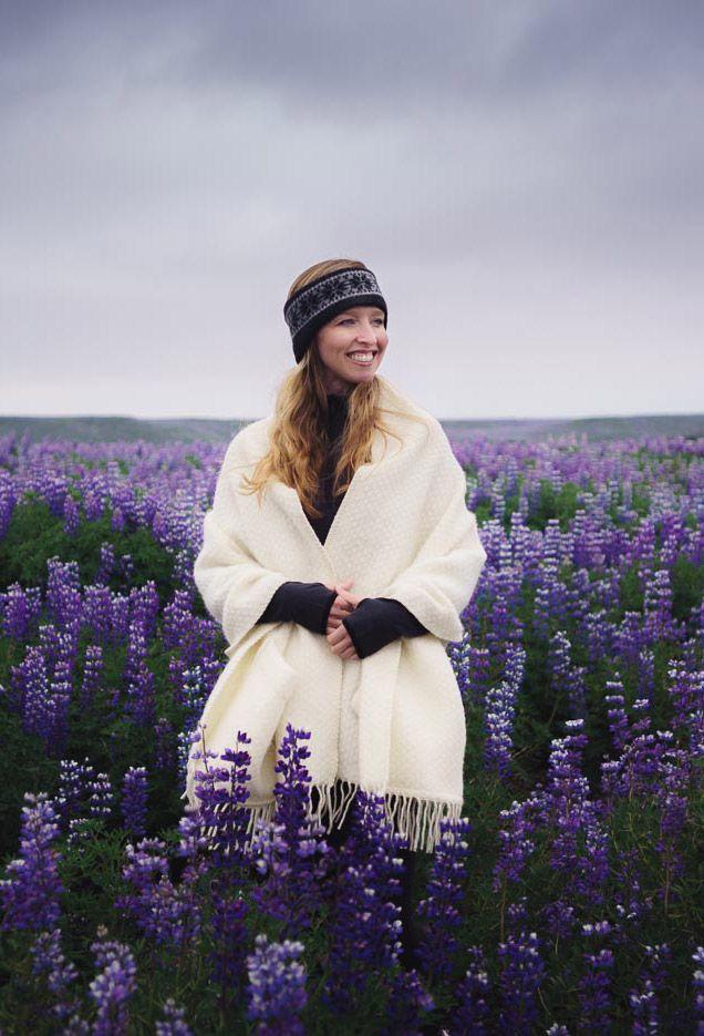 Lupine Summer Iceland Outfit on Stylish Travel Girl: ICEWEAR Norwegian headband, ICEWEAR FUNI shoulder blanket, ICEWEAR Freydis Polar Stretch top, Lucy Hatha leggings, Darn Tough socks, Brooks Launch running shoes