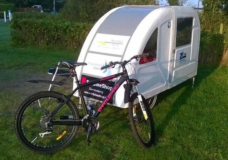 Der Wide Path Camper ist ein Wohnwagen für's Fahrrad. Leer wiegt er nur ca. 50 kg und lässt sich damit einfach ziehen. In dem ausklappbaren Anhänger haben zwei Sitze und ein Tisch Platz. Zum Schlafen lässt sich der Innenraum zu einem Bett umbauen. Wahlweise auch mit Küche und anderen Extras.
