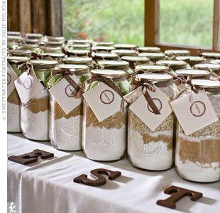 "super cute idea! A Rustic Wedding - The creative couple made their own favors: mason jars filled with ingredients for baking cookies -- guests could choose between chocolate chip and oatmeal raisin. They bought the jars online and filled them with the baking goods they bought at Sam's Club. Then, they decorated them with ribbon and recipe cards stamped with a ""thank-you."""