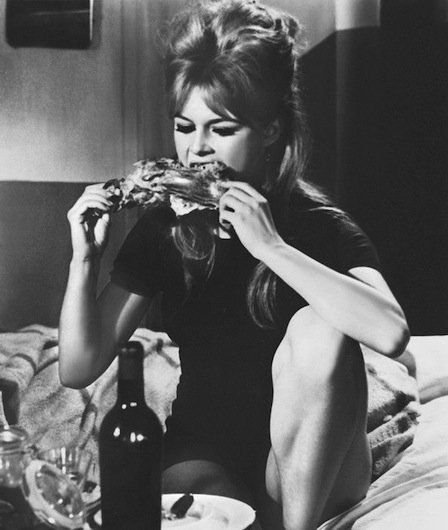 Brigitte Bardot - The French bombshell gnaws some chicken in 1960, with a bottle of red wine handy to wash it down.