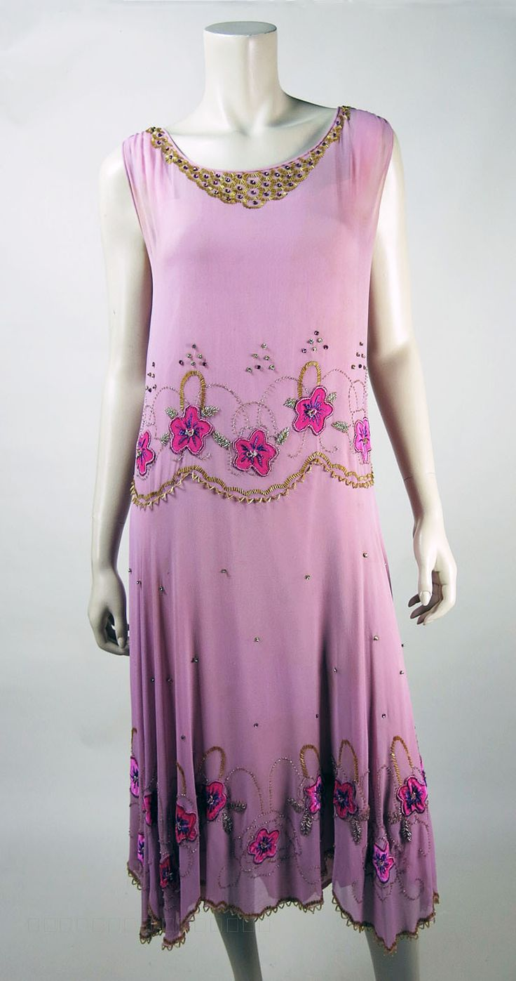 1920's Beaded Dress in rose-petal-pink silk chiffon with a joyful array of pretty embellishments including prong-set pink rhinestones, gold-tone metal beads in sequin cups, silver glass beads, gold bugle beads and lovely, fuchsia silk flower appliques with pink and purple embroidery. Beautiful and buoyant, sleeveless flapper silhouette with a drop-waist, an active, scalloped hemline on the flowing skirt and a separate, pale pink silk underdress, also with a scalloped hemline.  Front