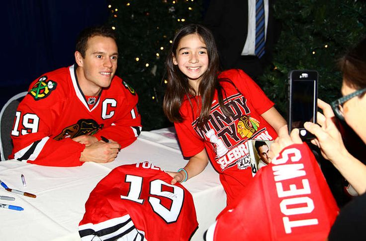 A #Blackhawks fan takes a photo with Jonathan Toews at the Season Ticket Holder holiday party.