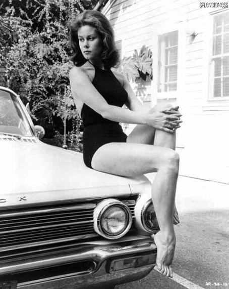 Elizabeth Montgomery sitting on a Buick.