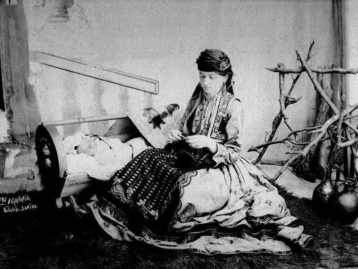 """Κλεισούρα Καστοριάς. Αναμνηστική φωτογραφία, η οποία απεικονίζει μία γυναίκα να πλέκει και δίπλα να κοιμάται στην κούνια το μωρό της. Ασπρόμαυρη ψηφιοποιημένη φωτογραφία, η οποία στο κάτω μέρος αριστερά αναγράφει τα εξής:""""MANAKIA Bitolia JANINA."""""""