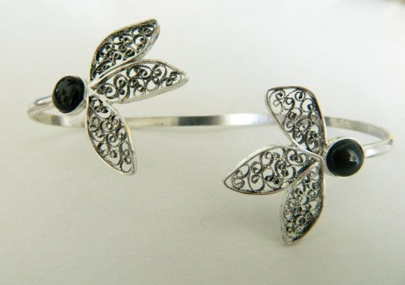 An exquisite one of a kind Elegant Filigree palm bracelet. It is a unique handmade piece of jewelry, made with lots of care and love and its ideal for daily casual or night wear. Its a combination of filigree elements made from fine 980 silver wire and with two black onyx gemstone on each side.  The size of the filigree palm cuff is 19 cm long. The size of the black onyx is 8 mm round. Its an open bracelet, so its adjustable.   Our jewelry comes in a gift box.  FILIGREE Filigree is one of…
