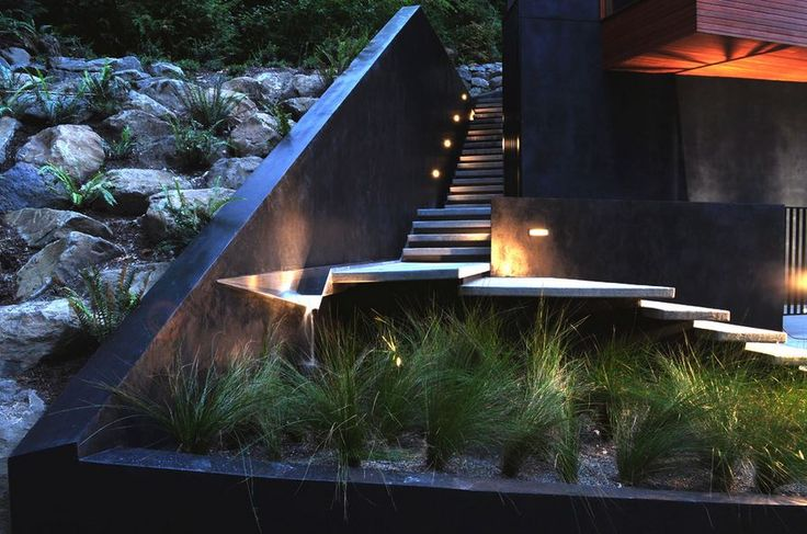 The dramatic steps rising above this grass garden and turning by the water feature are completely lit rather than simply bathed in a light that blurs the edges. This lighting scheme not only highlights this architectural feature and the surrounding landscape; it's a necessity with the nonuniform steps and lack of handrails. In contrast, the long stairway behind only needs sidelights set periodically into the wall to keep it lit and safe. [From 2.ink Studio]