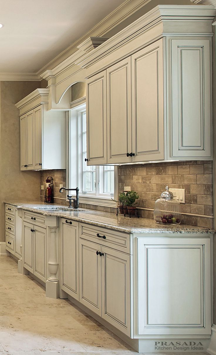 Classic kitchen.  Off white with clipped corners on the bump out sink, granite countertop, arched valance.  www.prasadakitchens.com