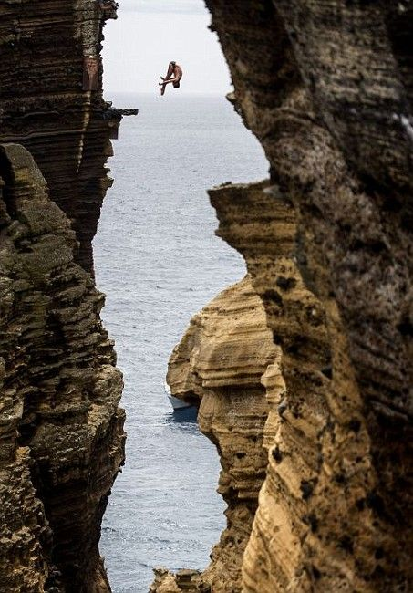 Blake Aldridge of Great Britain dives 29 metres from the rock monolith during the first round of the third stop of the Red Bull Cliff Diving World Series on July 20, 2012 in Islet Vila Franca do Campo, Azores, Portugal. (Photo by Dean Treml/Red Bull)