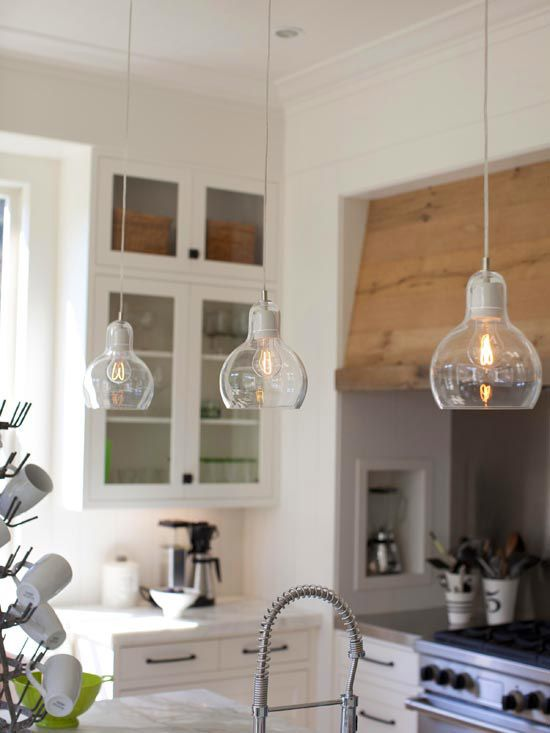 Industrial mingles with traditional for a style-setting look in the kitchen. Above the island, contemporary pendant lights with special filament bulbs accentuate the architectural interest of the stove hood and glass-front cabinetry. The simple lighting brightens the area and boosts the industrial feel provided by the large aluminum sink and modern faucet.