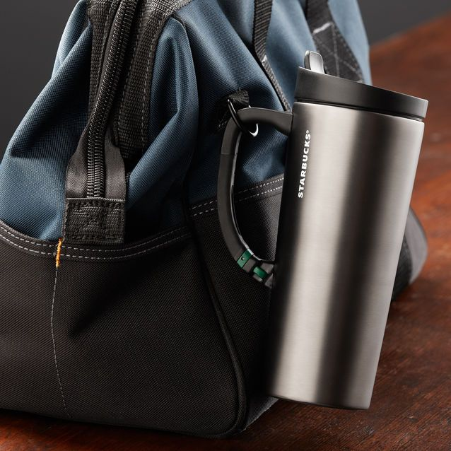 A double-walled stainless steel tumbler with flexible handle that clips to backpack or bag.