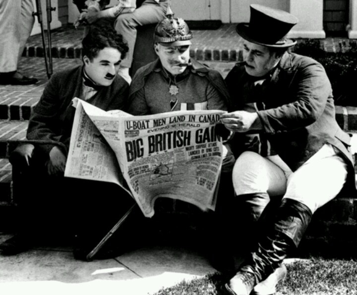 """Charlie Chaplin, Syd Chaplin, Henry Bergman reading news about the first world war during the filming of """"The Bond"""""""
