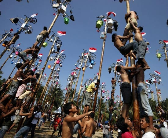 """Pali unti e scivolosi da scalare per raggiungere i ricchi premi legati in cima. E' un """"albero della cuccagna"""" in piena regola quello che tentano di scalare questi ragazzi indonesiani nel corso delle celebrazioni per il giorno dell'Indipendenza."""