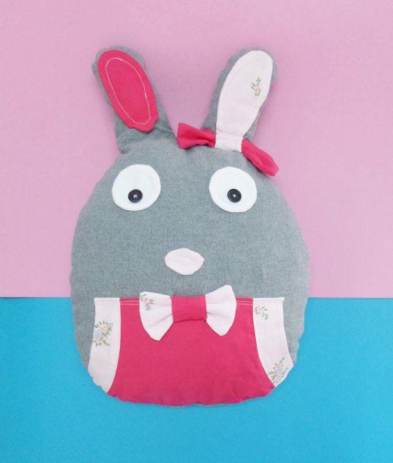 Conheça a nossa coelha, a Amora!  Almofada porta-pijama em forma de coelha. Com bolso na parte da frente e bolsa com fecho na parte de trás para guardar o pijama.  Utilização de tecidos cinzento escuro, rosa e estampado floral, todos de algodão.  Muito fofa e ideal para bebés e crianças. Pode colocar no berço do seu bebé. O enchimento é de boa qualidade.  O tamanho deste modelo é de 60 cm de altura por 40 cm de largura.  Na opção em cima pode escolher entre olhos com botões ou em feltro…