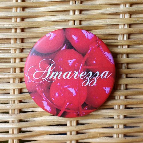 Pins - Amarezza  Spilletta metallica di 38mm di diametro, con finitura opaca.