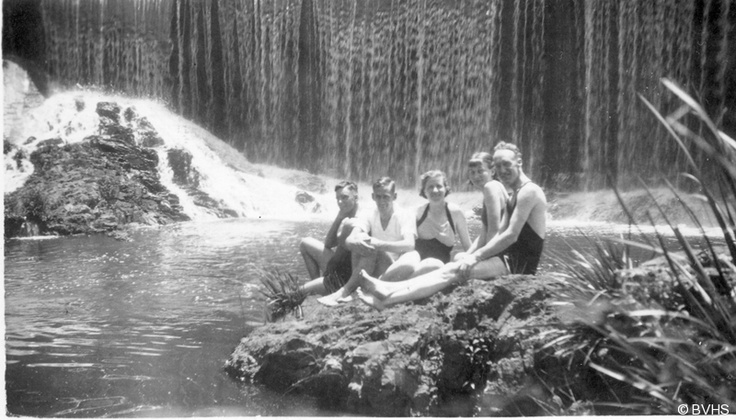 Black and white of a group of people (3 men and 2 women) in bathing costumes in front of a wall of water. Wilson's Creek.
