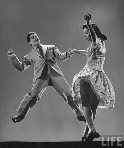 "Kaye Popp & Stanley Catron demonstrating a step of the Lindy Hop.  Photographer: Gjon Mili. LIFE, 8/23/1943. New York.    ""Swing dance"" is most commonly known as a group of dances that developed with the swing style of jazz music in the 1920s-1950s. The best known of these dances is the Lindy Hop, a popular partner dance that originated in Harlem in 1927 and is still danced today."