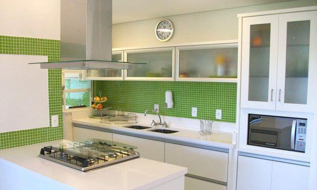 Pastilhas verdesO uso do branco nesse ambiente do escritório Teles e Marques foi uma opção para deixar a pequena cozinha mais ampla. No entanto, sem cor, ela ficaria muito fria e impessoal. As pastilhas verdes sobre a pia e a parede dão vida e um toque jovem ao espaço