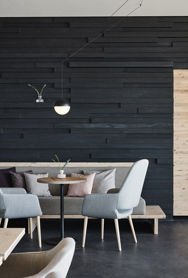 Create texture with black stained wooden boards on the walls, and keep it cosy with lots of neutral cushions - Loyly, Helsinki by Joanna Laajisto