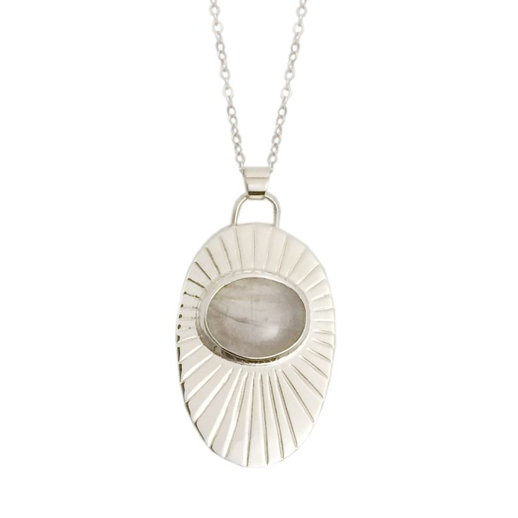 This sterling silver necklace features hand engraved rays emanating from a moonstone set in fine silver.