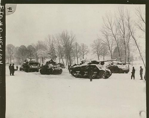 American troops of the 9th Armored Division prepare to evacuate Sherman tanks…