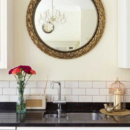 Small kitchen with neutral walls, white splashback tiles, black granite worktop and gold mirror