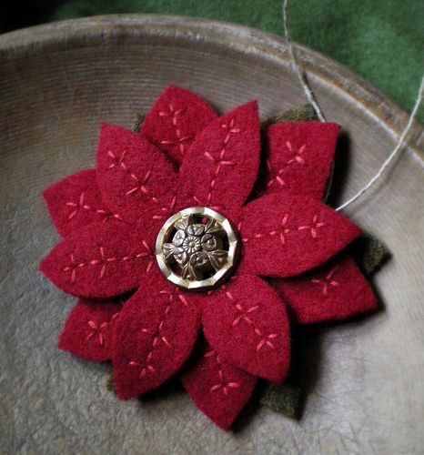 A poinsettia ornament made of felted coat wool and a vintage button for the center.