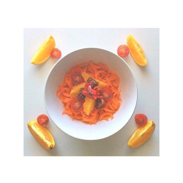 Carrot noodles with orange tomato fig and chia seed.  Clean raw healthy food