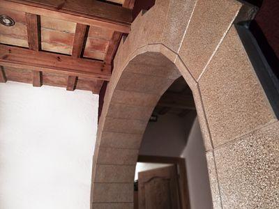 Arc en pedra i sostre amb llates de fusta i rajols artesans.  Construccions Madrona www.construmadrona.com