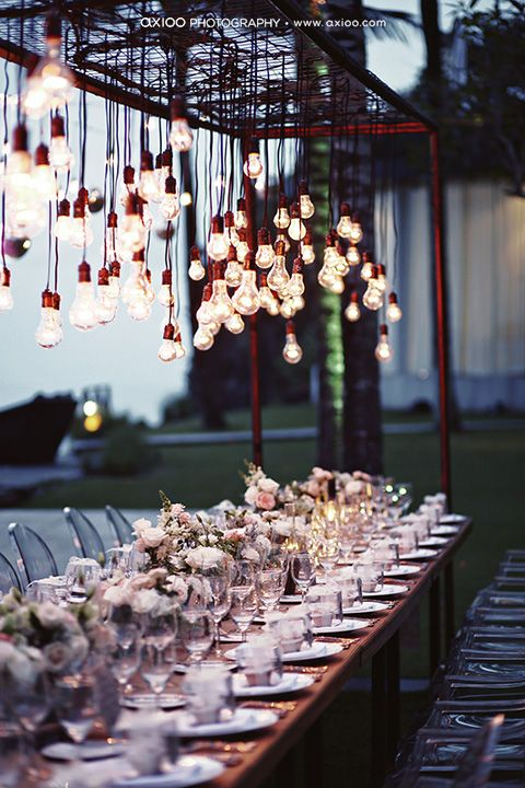 I love the edison bulb look here as well as the height of the floral arrangements (that way everyone can see one another!). A nice blend of industrial, rustic, and chic.