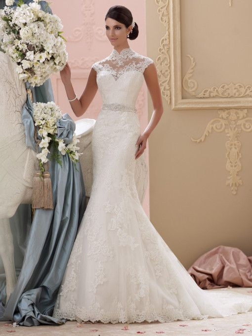 David Tutera for Mon Cheri - 115227 – Everly -     Modest wedding dress, Alencon lace and tulle over satin trumpet cage dress with cap sleeves, scalloped lace and illusion high neckline over a deep sweetheart bodice, satin belt adorned with center hand-beaded jeweled motif at natural waistline, full illusion and lace back finished with covered button closures over a low deep V-back bodice, tulle and Alencon lace appliqué cage skirt with scalloped hemline and chapel length train skims over a…