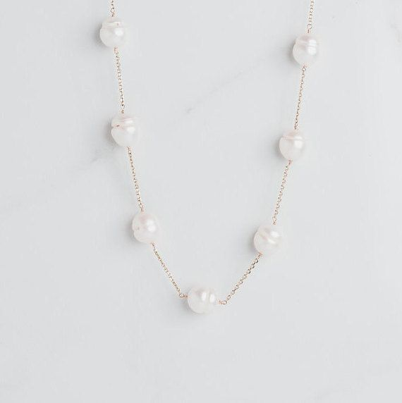 A statement making classic pearl necklace, perfect for brides and beyond.  Hand crafted in 14kt white or yellow gold, this genuine freshwater pearl station necklace is perfect for any occasion. The 9-11mm freshwater pearls were hand selected to match. A delicate but sturdy chain links the pearls together, and the lobster claw clasp makes it beyond easy to put this beauty on by yourself. We love this classic preppy necklace for everyday, weddings, bridesmaids gifts, holiday gifts, and special…