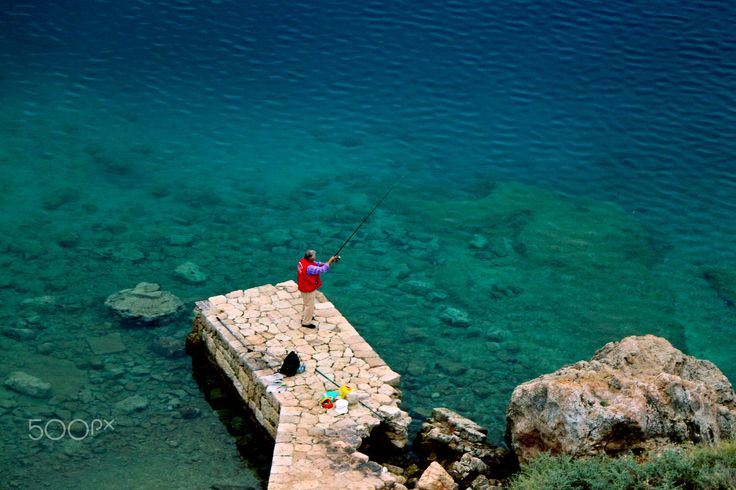 The fisherman - Fishing over the ancient port of Heraion in Loutraki region, Peloponnese, Greece.