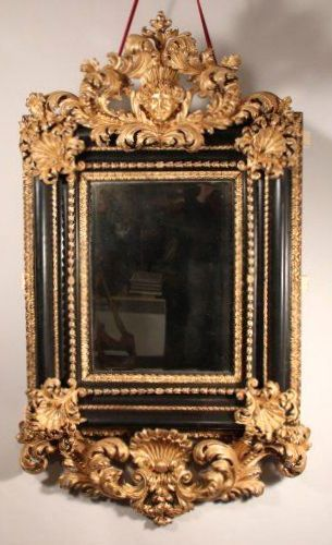 Large mirror blackened giltwood made in Italy in 1700 by a talented artist. The realization of the sculpture of this mirror is both admirable finesse by the care taken to bring lightness to her yet powerful execution. We do not know the Italian artisan active from the late seventeenth century who was able to achieve this masterpiece of carpentry that does not fade in a perfectly preserved as a whole and for its burnished gilding