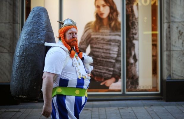 A man wearing an Obelix costume walks through  Cologne city centre at the start of the carnival season in Germany.