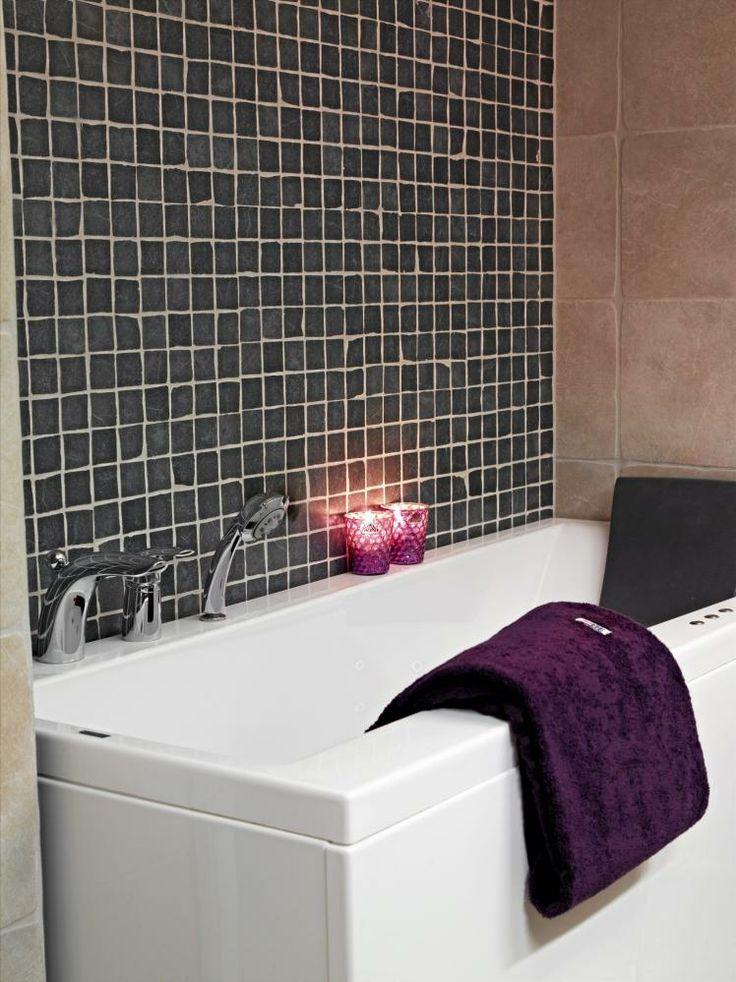 Veggene på badet har fått ulike fliser. Veggen bak badekaret er dekket av svarte, små mosaikkfliser, mens den møtende veggen har fått store fliser i en varm beigefarge.