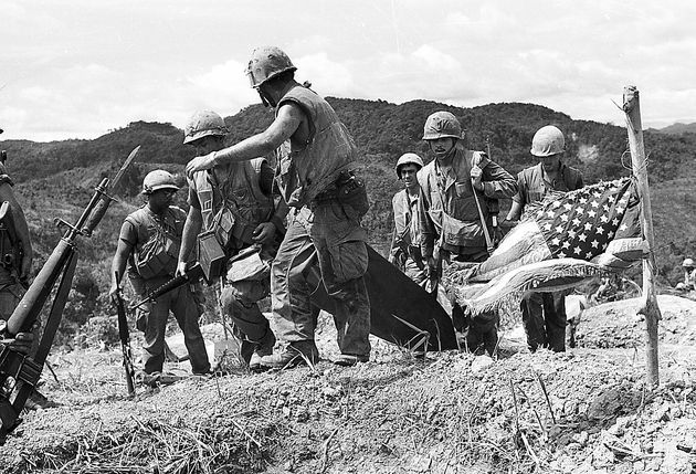 U.S. Marines carry the body of one of the 18 slain comrades on a south Vietnamese hilltop south of Khe Sahn to an evacuation point on June 17, 1968, during the Vietnam War. The men died more than a week ago in a clash near a road being built by North Vietnamese forces from nearby Laos into extreme northwestern south Vietnam. An American flag, found on one of the bodies, flies at half staff (AP Photo/Henri Huet)
